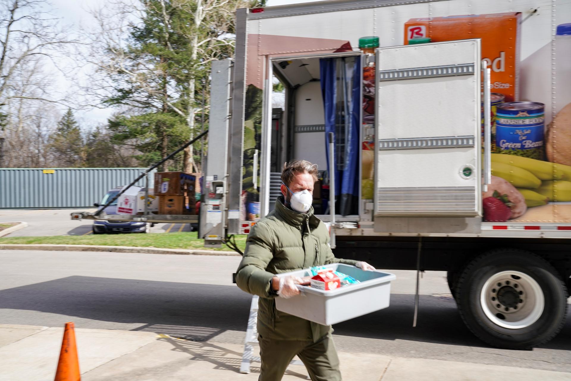 Volunteer delivers groceries from the My Neighborhood Mobile Grocery truck.