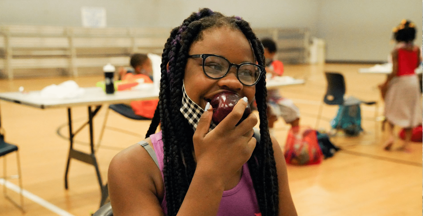 Food Distribution in Schools Girl Eating Apple COVID News