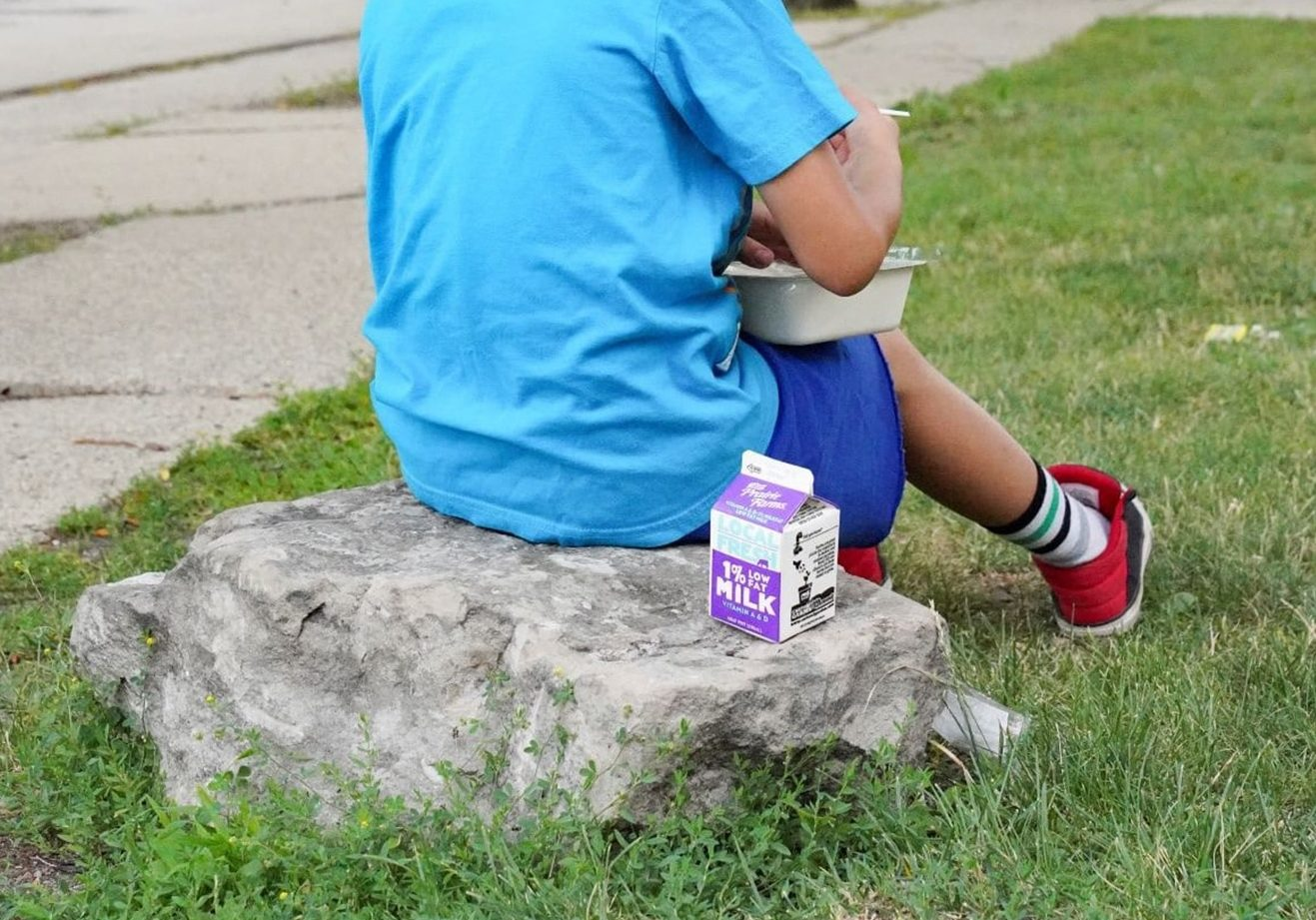 Little Boy On A Rock With Milk